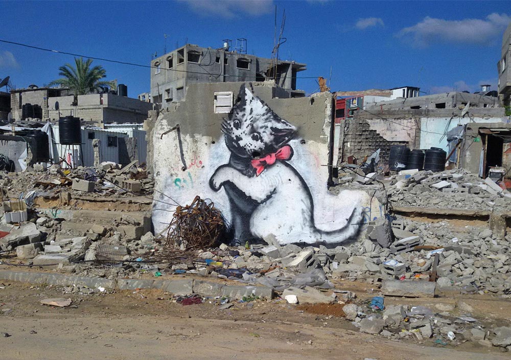A mural of a cute kitten by Banksy surrounded by damage, Gaza City.