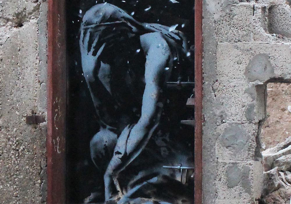 A piece by Banksy surrounded by bomb damage, Gaza City (detail)