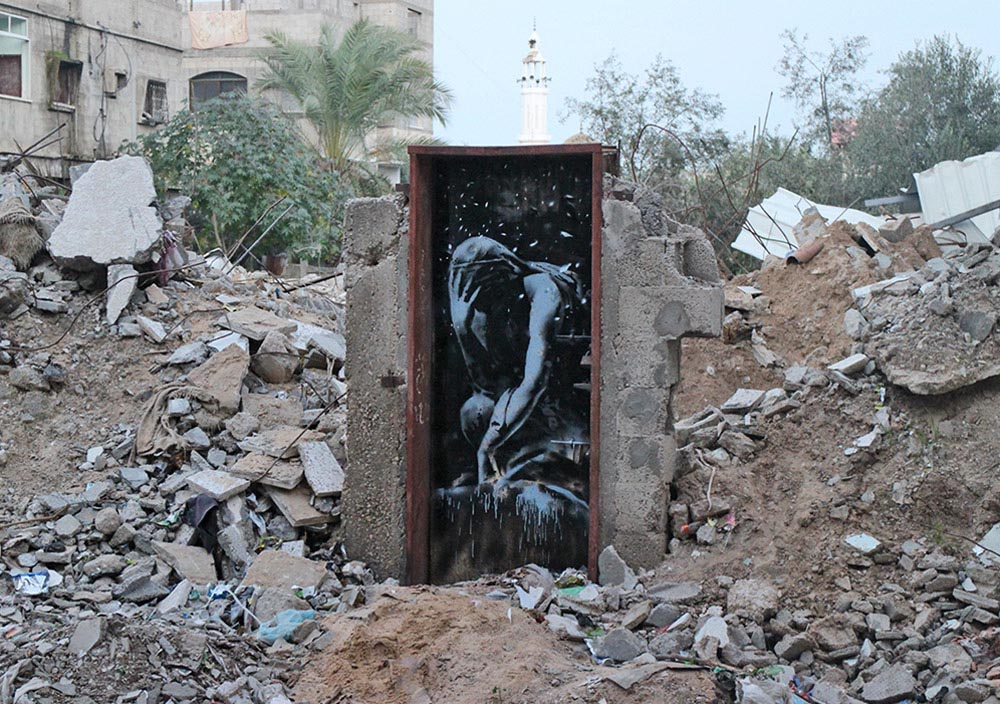 A piece by Banksy surrounded by bomb damage, Gaza City